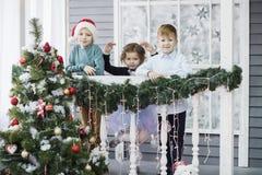 Peu enfants en pr?vision de nouvelle ann?e et de No?l Trois petits enfants ont l'amusement et jouent pr?s de l'arbre de No photographie stock libre de droits