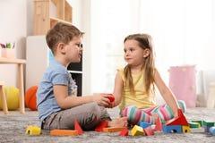 Peu enfants jouant avec les blocs colorés images stock