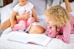 Peu enfants regardant par le livre tout en se reposant sur le lit avec la mère image libre de droits