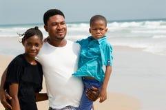 Peu famille africaine à la plage images stock