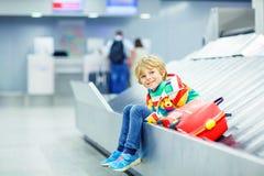Peu a fatigué le garçon d'enfant à l'aéroport, voyageant Photos stock