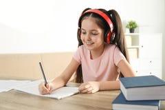Peu fille écrivant des notes de musique à la table image stock