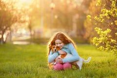 Peu fille étreignant son ami un chien dans l'extérieur images stock