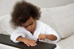 Peu fille afro-américaine peint des clous sur des mains photographie stock libre de droits
