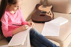Peu fille avec des notes de musique d'écriture de guitare image libre de droits