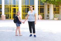 Peu fille avec le sac d'école ou sacoche marchant à l'école avec la grand-mère images libres de droits
