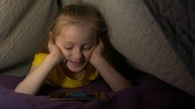 Peu fille avec le téléphone sur le lit banque de vidéos