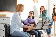 Peu fille avec son professeur et mère à la leçon de musique images libres de droits