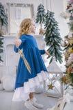 Peu fille avec une branche d'or dans des ses mains dansant près de l'arbre de Noël photo libre de droits