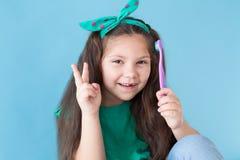 Peu fille avec une dent avec une bosselure de brosse à dents photo stock