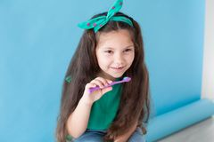 Peu fille avec une dent avec une bosselure de brosse à dents image stock