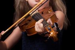Peu fille blonde jouant le violon sur le fond noir images libres de droits