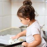 Peu fille d'enfant en bas ?ge faisant la boulangerie de g?teau dans la cuisine photographie stock libre de droits