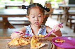 Peu fille d'enfant ont plaisir ? manger de la pizza sur la table photos stock