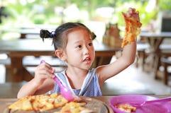 Peu fille d'enfant ont plaisir ? manger de la pizza sur la table image stock