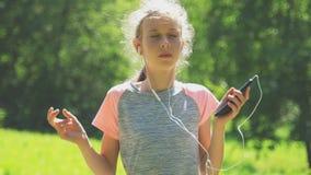 Peu fille dans des écouteurs écoutant l'extérieur de musique banque de vidéos