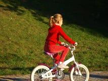 Peu fille dans des vêtements rouges montant son vélo en parc de ville photographie stock libre de droits