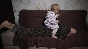 Peu fille dans le peignoir r?veillant son p?re L'homme dort sur le divan banque de vidéos