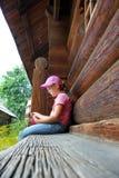 Peu fille dans un chapeau rose se repose sur un banc près d'une maison en bois photos stock