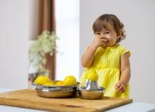 Peu fille dans une robe jaune prépare la limonade image stock