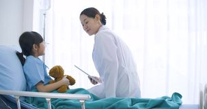 Peu fille de yound parlant au docteur féminin dans l'unité de soins intensifs banque de vidéos
