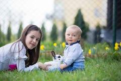 Peu fille et son frère de bébé, jouant avec le lapin blanc dans p photos libres de droits