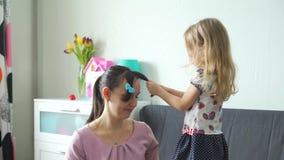 Peu fille faisant la coiffure à sa mère clips vidéos