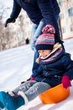 Peu fille glissant vers le bas de la colline de neige avec son père photographie stock