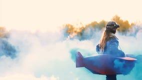 Peu fille heureuse d'aviateur tournant dans l'avion de carton d'amusement avec de la fumée bleue de couleur feignant pour être un clips vidéos