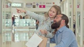 Peu fille indiquant loin, montrant quelque chose son père au centre commercial banque de vidéos