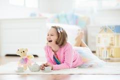 Peu fille jouant avec la maison de poupée Enfant avec des jouets photographie stock libre de droits