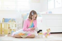 Peu fille jouant avec la maison de poupée Enfant avec des jouets photo stock
