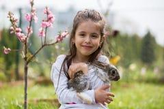 Peu fille jouant avec le lapin blanc en parc un été ensoleillé photo libre de droits
