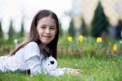 Peu fille jouant avec le lapin blanc en parc un été ensoleillé photographie stock libre de droits