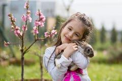 Peu fille jouant avec le lapin blanc en parc un été ensoleillé image stock