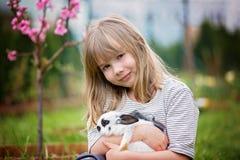 Peu fille jouant avec le lapin blanc en parc un été ensoleillé image libre de droits