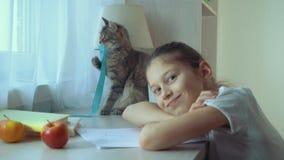 Peu fille jouant avec son chat d'animal familier et regardant la caméra banque de vidéos