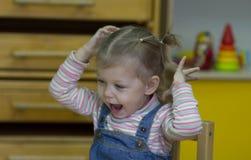 Peu fille jouant et étudiant sur des leçons dans le jardin d'enfants photo libre de droits