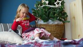 Peu fille jouant la tablette près de l'arbre de Noël banque de vidéos