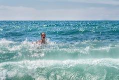 Peu, fille joyeuse dans éclabousse des vagues sur la mer photo stock
