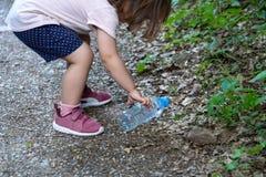 Peu fille, mère enceinte et grand-mère nettoyant la forêt de plastiques photo libre de droits