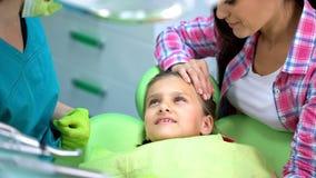 Peu fille mignonne au dentiste, contrôle régulier des dents, stomatologie pédiatrique image libre de droits