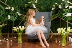 Peu fille mignonne avec les cheveux blonds dans une robe blanche tenant un petit chien et des fleurs blanches, des lis et des orc photo stock