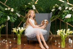 Peu fille mignonne avec les cheveux blonds dans une robe blanche tenant un petit chien et des fleurs blanches, des lis et des orc photographie stock