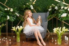 Peu fille mignonne avec les cheveux blonds dans une robe blanche tenant un petit chien et des fleurs blanches, des lis et des orc images stock