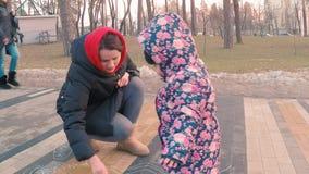 Peu fille mignonne dans une veste rose colorée dessine avec une jeune mère avec la craie sur un trottoir près du terrain de jeu d clips vidéos