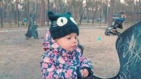 Peu fille mignonne dans une veste rose colorée dessine avec la craie sur un tableau noir sous forme de dinosaure sur les enfants clips vidéos
