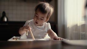 Peu fille mignonne dessine un crayon sur le papier L'enfant frappe sur le papier avec un crayon banque de vidéos