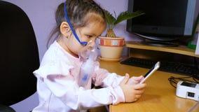 Peu fille mignonne est traité avec un nébuliseur et utilise un téléphone portable banque de vidéos