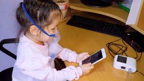 Peu fille mignonne est traité avec un nébuliseur et utilise un téléphone portable clips vidéos
